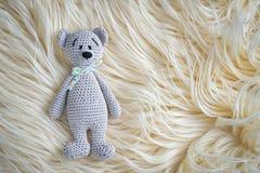 Bear. Cute handmade crochet amigurumi teddy bear doll laying on the white fur with copy space royalty free stock image