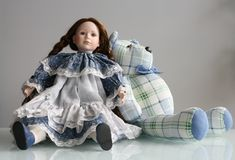 Bear with doll. Bear with a blue bow and doll in blue dress sitting on a background of white walls royalty free stock photography