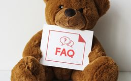 Bear doll with an FAQ card royalty free stock image