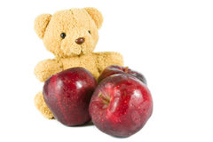 Bear doll give fresh red apple. On white Stock Images
