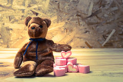 Bear doll with marshmallow heart. Royalty Free Stock Images