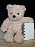 Bear doll and notebook on the wood table Royalty Free Stock Images