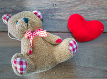 Bear doll and red heart. Bear doll with red heart on wooden background Royalty Free Stock Photography