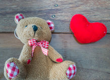 Bear doll and red heart. Bear doll with red heart on wooden background Stock Photography
