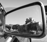 Bear doll on reflection of car rear mirror in black and white. Colour looking up to the sky Royalty Free Stock Image