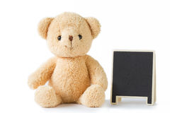 Bear doll sitting with blackboard on white background isolated. Royalty Free Stock Photos