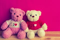 Two bears doll sitting together, Valentine`s day and love concept. Bear doll on wooden plank table top with red pink color background, Valentine`s concept Stock Photography