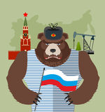 Bear with ear flaps with  flag of Russia. Background of  Moscow. Kremlin and oil rigs. Vector illustration Stock Photography