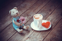 Bear with flower. And cup of coffee on wooden background Stock Photography
