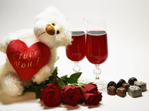 Bear with a heart against the background of glasses, roses and c Royalty Free Stock Photo