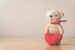 Bear with Heart on wood table Stock Photos