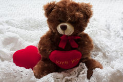 Bear with hearts on a white knitted cloth. Valentine`s Day card. Teddy bear with a heart. A red heart. White knit fabric Stock Photo