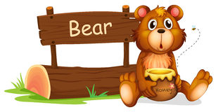A bear holding a honey beside a wooden signboard Royalty Free Stock Image