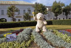 A bear holding olympic torch shown in a city park. Stock Photo