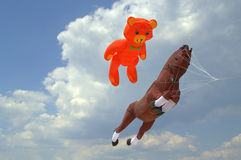 Bear and horse kites soar in the clouds Stock Photos
