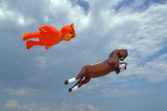 Bear and horse kites soar in the clouds Royalty Free Stock Image