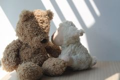 Bear and lamb toy sitting by the window in shadows. Bear and lamb sheep toy sitting by the window in shadows stock photography