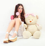 Bear and lollypop. Cute young woman dressed as a doll holding big bear Stock Photography