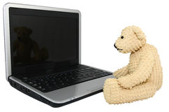 Bear With Mini Lap Top Computer. A small teddy bear sits at the keyboard of a mini laptop computer. Bear and computer isolated on a white background Royalty Free Stock Photography