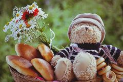 Bear with pastries. Teddy bear in a basket with a bouquet of flowers and cakes stock photos