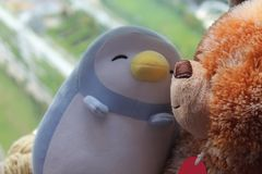 Bear and penguin toy sitting by the window in shadows Royalty Free Stock Photos