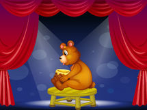 A bear with a pot of honey sitting at the stage Stock Photography