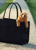 Bear in purse. A teddy bear sitting in a black purse. the background is a stone wall which is out of focus Stock Photography