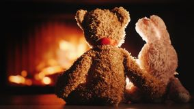 Bear and rabbit in a hug sit by the fireplace. Valentine`s Day concept