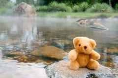 Bear on the rocks. A teddy bear sits on a rock at a hot spring Stock Photos