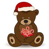 Bear in Santa Claus hat holding a candy. This is file of EPS10 format Royalty Free Stock Image