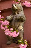 Bear sculpture among the cherry blossom flowers. Beautiful springtime background Stock Photo