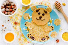 Bear-shaped pancakes with honey and nuts - creative idea for chi Royalty Free Stock Images