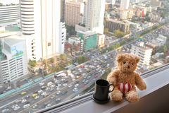 A bear sitting next to the window with blurred traffic congestion Royalty Free Stock Photos