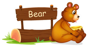 A bear sitting beside a wooden signage Stock Images