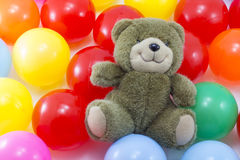 Bear toy and colorful plastic ball background Royalty Free Stock Photos