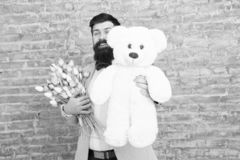 Bear toy. Enjoying spring holiday. Bearded man with tulip bouquet and bear. Spring gift. Bearded man with flowers. Cute stock photo