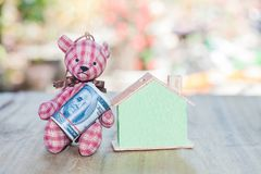 Bear toy save money to buy a house Royalty Free Stock Photography