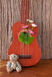 Bear toy with ukulele on wooden backgrounds. Music Stock Image