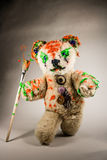 Bear toy walks with painted paintbrush Royalty Free Stock Images