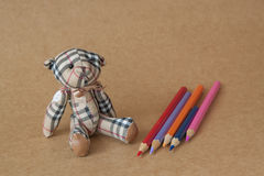 Bear toys on texture of paper backgrounds and pencils Stock Image