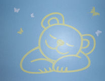 Bear on the wall. Sleep bear on light blue wall background and flying butterfly Stock Photo