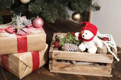 Bear wearing Santa hat with Christmas gift boxes on a white carpet at night. Many gifts in craft paper with a red ribbon under the tree. wooden box with snow royalty free stock photos