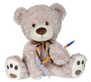 Bear Writing on Pad. Beige Teddy Bear writing on a note pad Royalty Free Stock Photo
