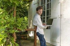 Bearbed modemodell som ler med bärbar datordatoren under per Royaltyfri Foto