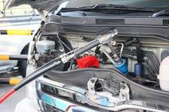 Bearbeiten Sie pumpenden Gasbrennstoff in einem Packwagen an der Tankstelle maschinell Stockfotografie