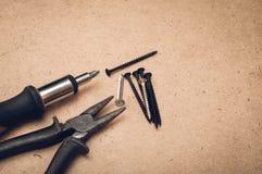 Bearbeiten Sie Schraubenzieher, Schraube und Zangen auf einem hölzernen Hintergrund lizenzfreie stockfotos