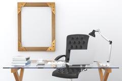 Bearbeiten Sie Schreibtisch mit einem Laptop und einem leeren Bilderrahmen auf der Wand, m Lizenzfreie Stockfotos