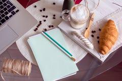 Bearbeiten Sie Schreibtisch mit Laptop, Kaffee und Hörnchen Lizenzfreies Stockbild