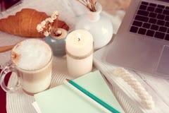 Bearbeiten Sie Schreibtisch mit Laptop, Kaffee und Hörnchen Lizenzfreie Stockfotografie