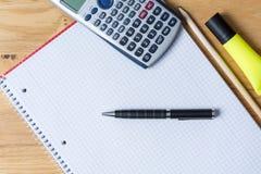 Bearbeiten Sie Schreibtisch mit Notizblock, Taschenrechner und Biro auf Holztisch stockbild